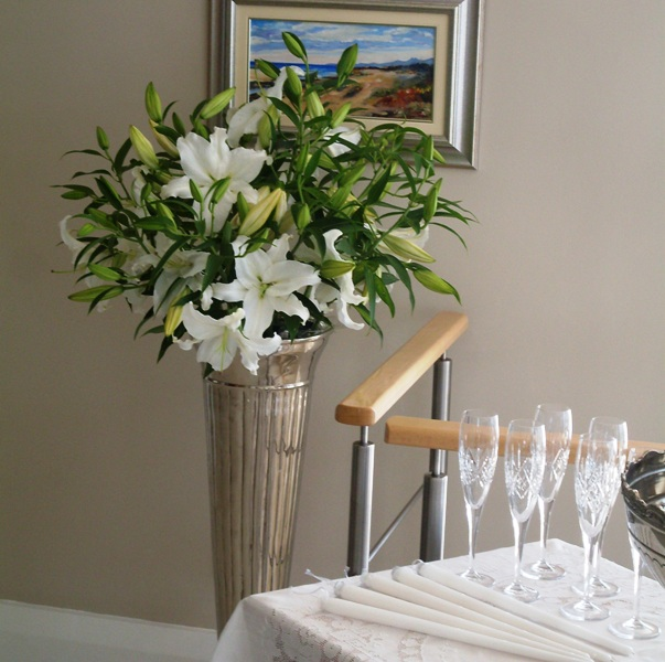 White casablanca lilies in a tall silver vase