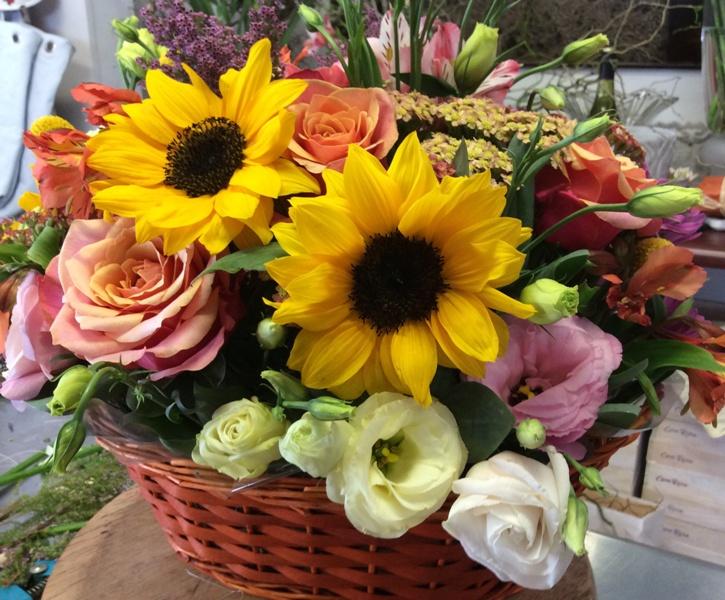 bright flower arrangement in a round basket